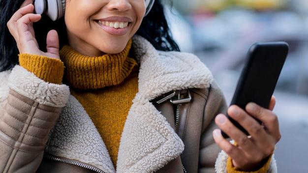 Smiley afro-amerikaanse vrouw luisteren naar muziek via koptelefoon