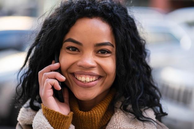 Smiley afro-amerikaanse vrouw praten over de telefoon