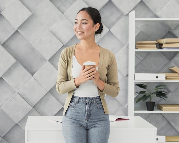 Smiley aziatische vrouw die een koffiemok houdt