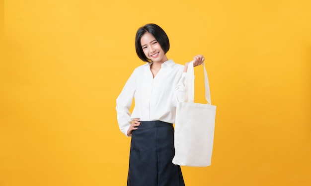 Smiley aziatische vrouw in casual witte t-shirt staan en houden zak canvas stof voor mockup logo op de gele muur