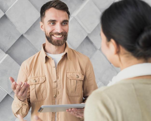 Smiley bebaarde man bespreken met zijn collega