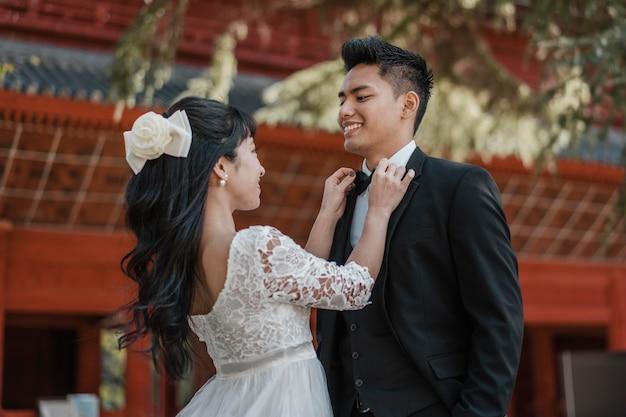 Smiley-bruid maakt de vlinderdas van de bruidegom vast
