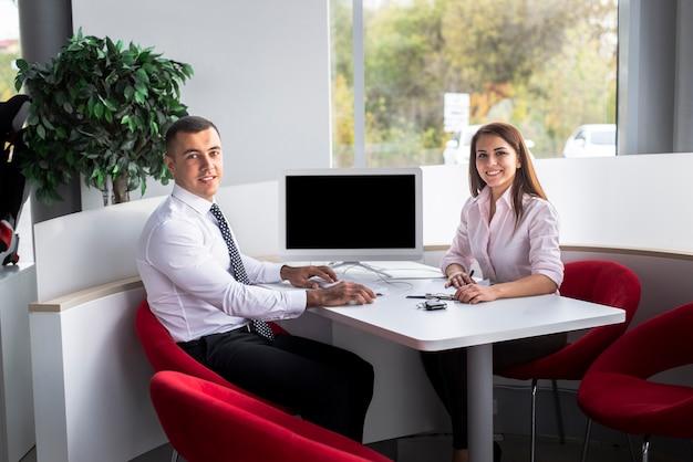 Smiley dealers autoverkopers op kantoor