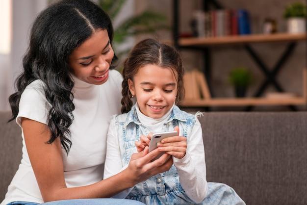 Smiley dochter met behulp van moeder telefoon