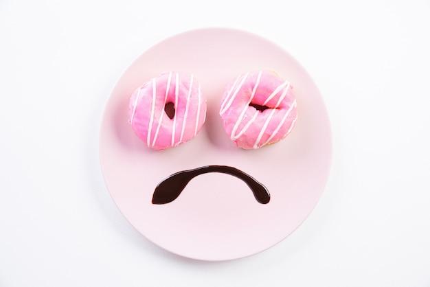 Smiley droevig gezicht bezorgd over overgewicht gemaakt op schotel met donuts
