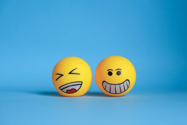Smiley en lach emoticon geïsoleerd op blauwe achtergrond