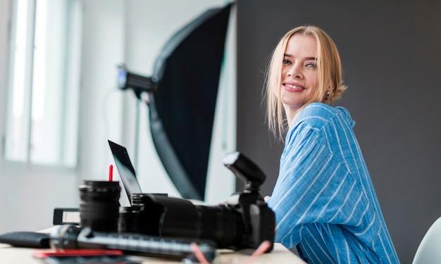 Smiley fotograaf vrouw zitten aan haar bureau