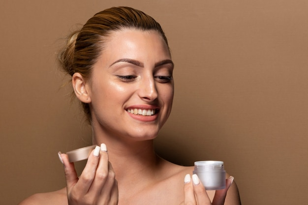 Smiley jong meisje testen huidverzorgingsproducten