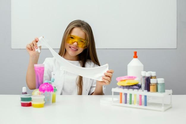 Smiley jong meisje wetenschapper experimenteren met slijm