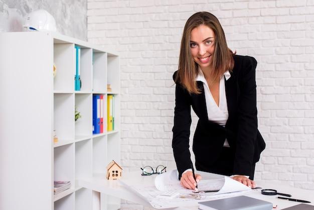 Smiley jonge architect die een plan ondertekent