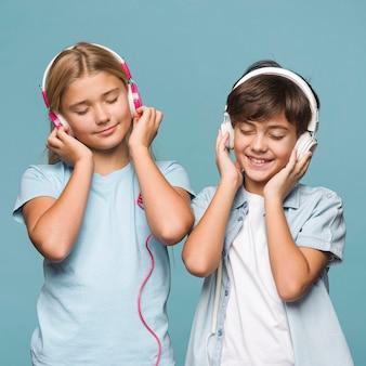 Smiley jonge broers en zussen luisteren muziek