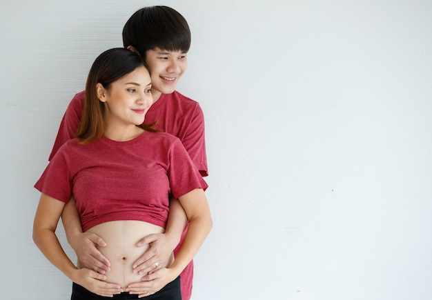 Smiley jonge man en vrouw staan samen op een witte achtergrond. een man omhelst een zwangere vrouw en legt zijn hand op haar buik. mensen, familie en lifestyle concept. ruimte kopiëren.