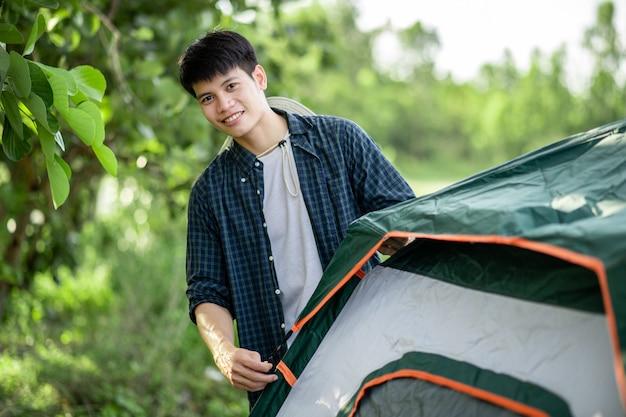 Smiley jonge reiziger man zet een tent op de camping in het bos op zomervakantie