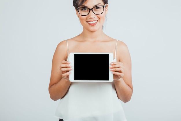 Smiley jonge vrouw die een tablet presenteert