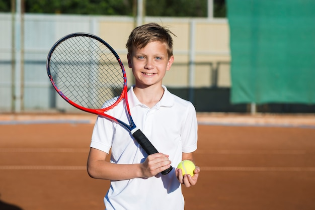 Smiley jongen met tennisracket
