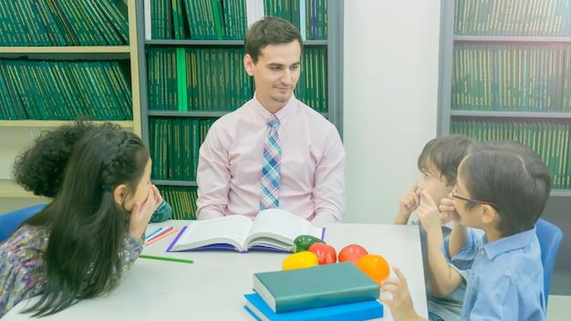 Smiley kaukasische leraar en groepering van aziatische kinderen student leren