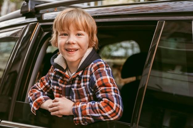 Smiley-kind in de auto tijdens een roadtrip