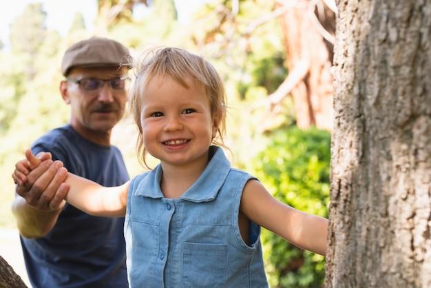 Smiley kleine jongen die bomen met opa onderzoekt