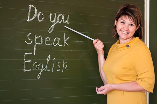 Smiley leraar uitleggen op schoolbord