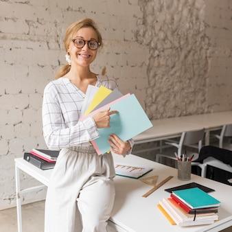 Smiley leraar wijzend op boeken