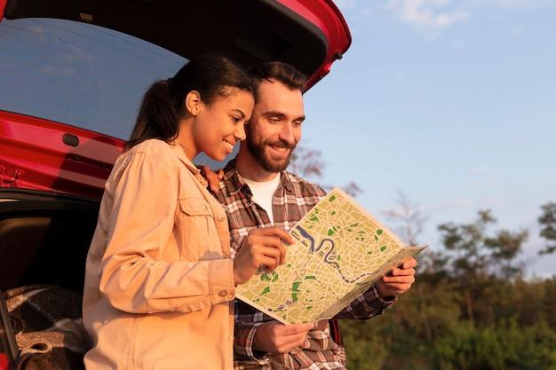Smiley man en vrouw die een kaart controleren