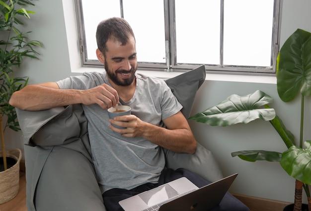Smiley man met koffie tijdens het werken vanuit huis op laptop