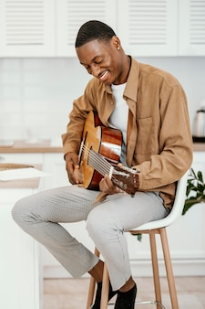 Smiley mannelijke musicus thuis op stoel gitaarspelen