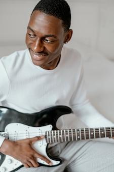 Smiley mannelijke muzikant met elektrische gitaar