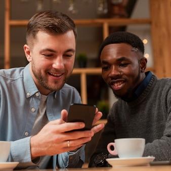 Smiley mannelijke vrienden die op mobiel kijken