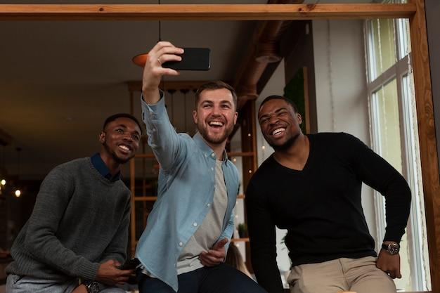Smiley mannelijke vrienden die selfies nemen