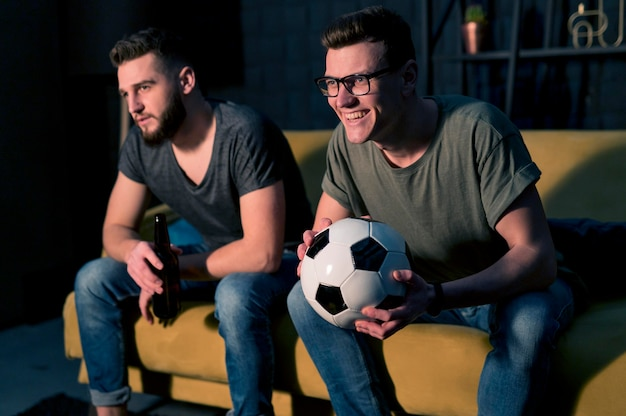 Smiley mannelijke vrienden kijken samen naar sport op tv terwijl ze voetbal vast houden