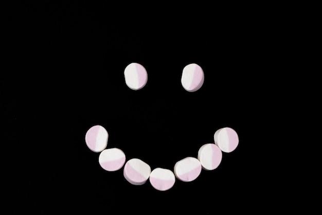 Smiley marshmallow snoep op een zwarte achtergrond. detailopname