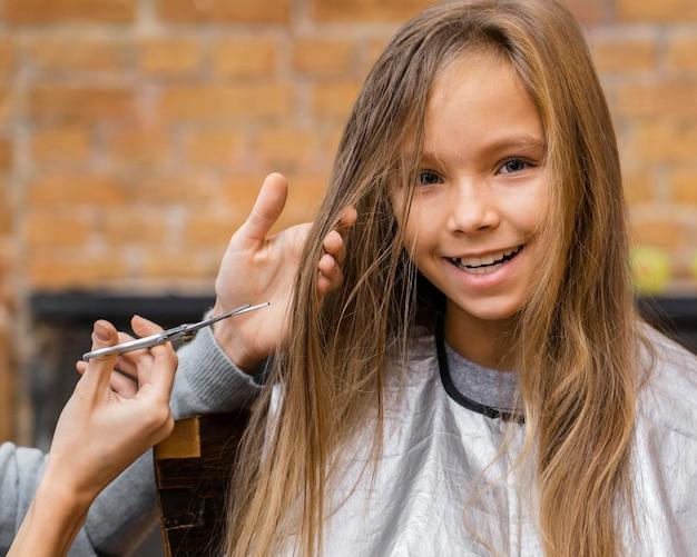 Smiley meisje haar haren knippen bij de kapper