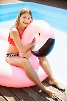 Smiley meisje knuffelen een flamingo floatie