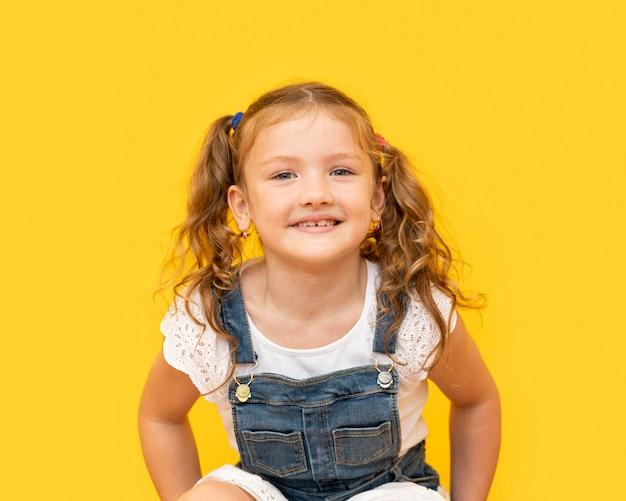 Smiley meisje met gele achtergrond