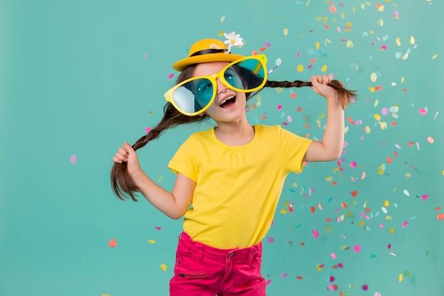 Smiley meisje met grote zonnebril en confetti
