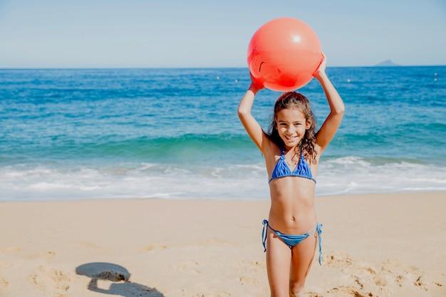 Smiley meisje spelen met een bal op het strand
