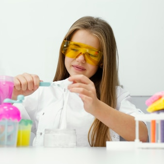Smiley meisje wetenschapper met veiligheidsbril plezier maken van slijm in het lab
