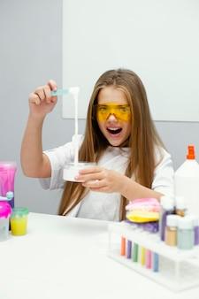 Smiley meisje wetenschapper plezier maken van slijm in het laboratorium