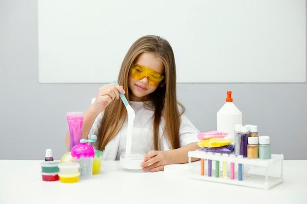 Smiley meisje wetenschapper slijm maken in het laboratorium