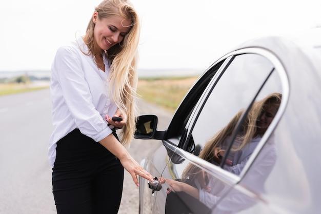 Smiley mooie vrouw die de autodeur opent