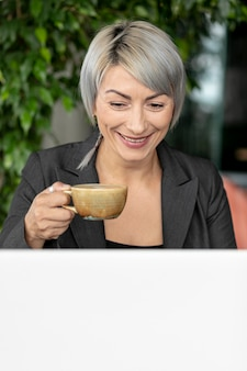 Smiley mooie vrouw die van koffie geniet