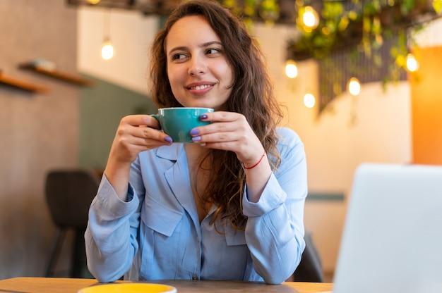 Smiley-nomadenvrouw met koffie