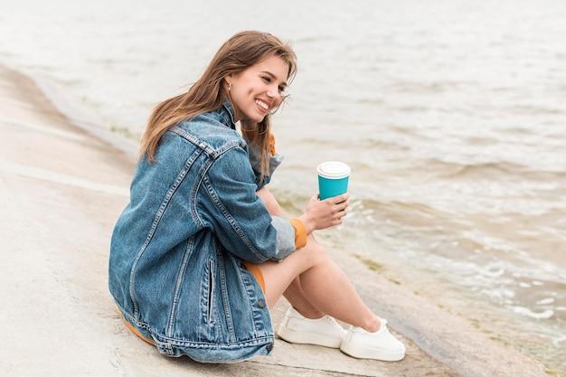Smiley oman met koffie aan zee