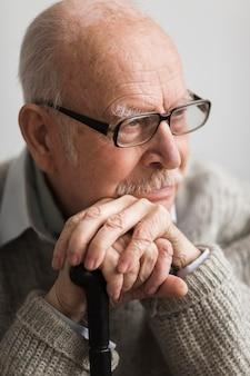 Smiley oude man in een verpleeghuis met stok