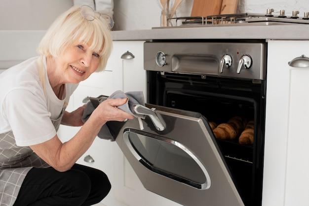Smiley oude vrouw die de deur van de oven opent Gratis Foto