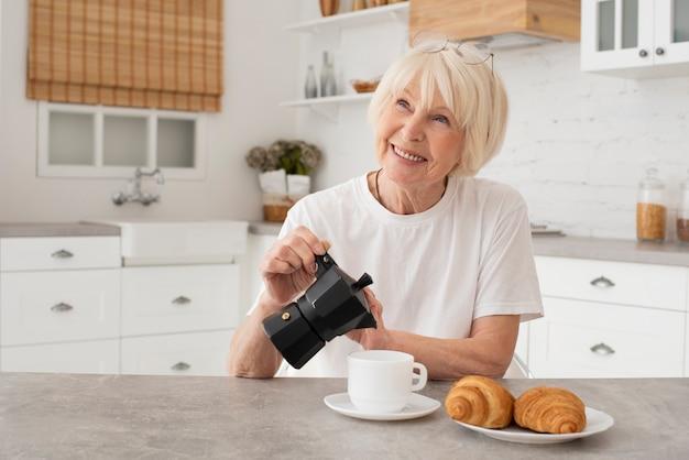 Smiley oude vrouw die de ketel houdt