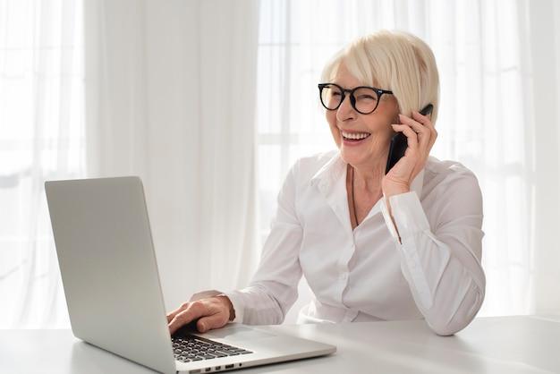Smiley oude vrouw praten aan de telefoon