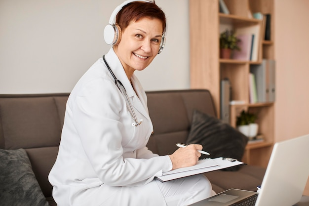 Smiley oudere covid herstelcentrum vrouwelijke arts met koptelefoon en klembord