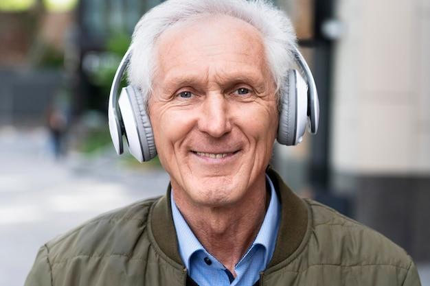 Smiley oudere man in de stad die naar muziek luistert op een koptelefoon